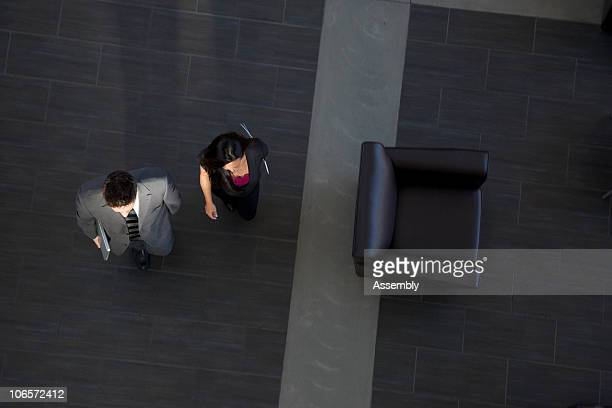 Two businesspeople walking through foyer