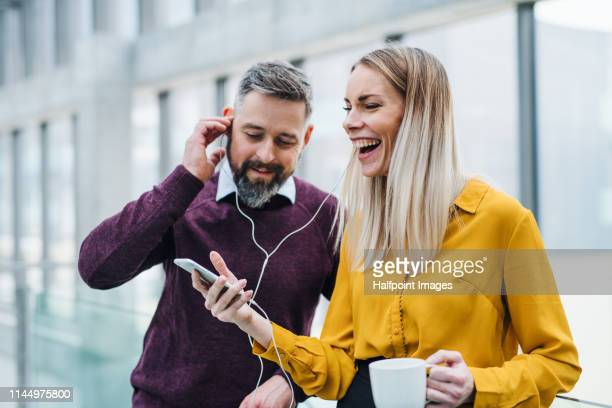 two businesspeople with a cup of coffee in a modern office, using smartphone and earphones. - fare una pausa foto e immagini stock