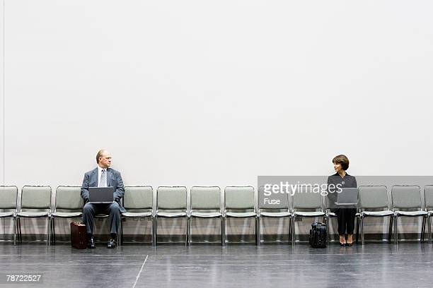 two businesspeople with laptops looking at each other - mismatch stock pictures, royalty-free photos & images