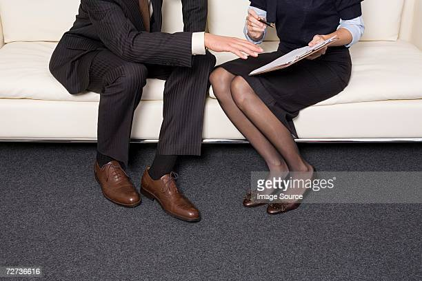 two businesspeople working on a sofa - human leg stock photos and pictures