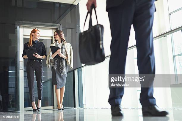 Two businesswoman exiting the elevator and walking