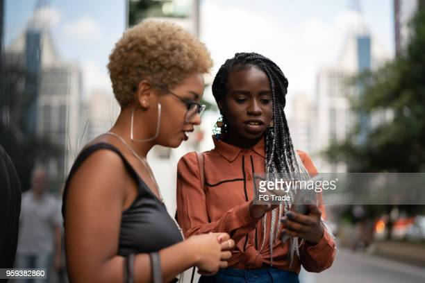 two businesswoman get directions on mobile - doing a favor stock pictures, royalty-free photos & images
