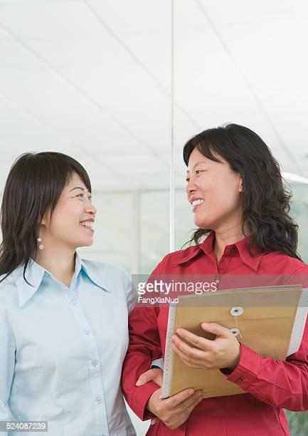2 つのビジネスウーマンのオフィス、笑顔で話している