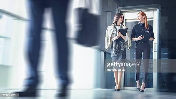 2 つの女性実業家歩くと話し