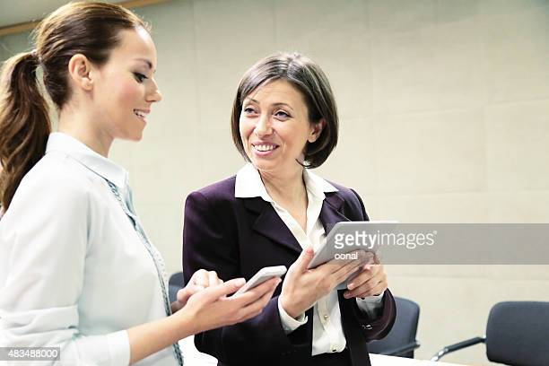 Two businesswoman working on mobile devices
