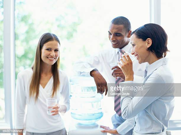two businesswomen and a businessman drinking water from a water cooler in an office