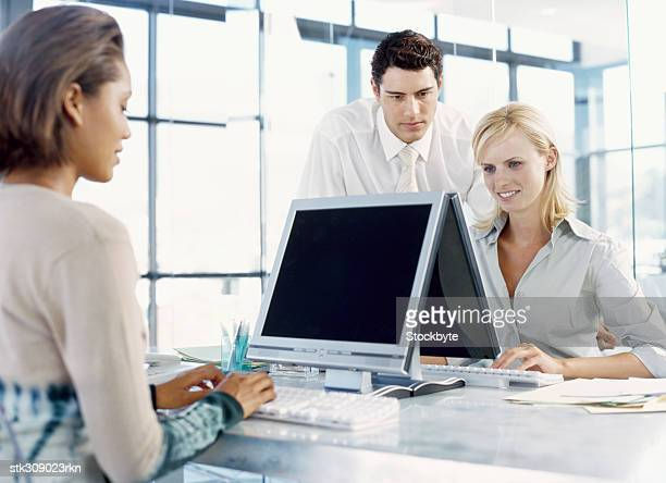 two businesswomen and a businessman sitting in front of a computer in an office - formal businesswear stock pictures, royalty-free photos & images
