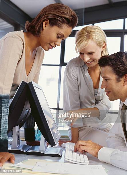 two businesswomen and a businessman using a computer in an office