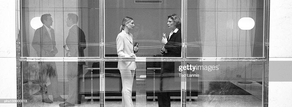 Two businesswomen behind large glass window, B&W : Stockfoto