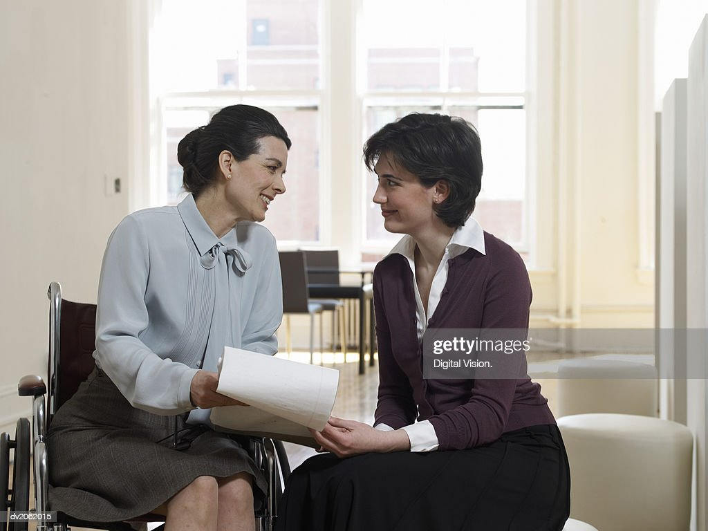 Two Businesswomen Examining a Document Together : Stock Photo