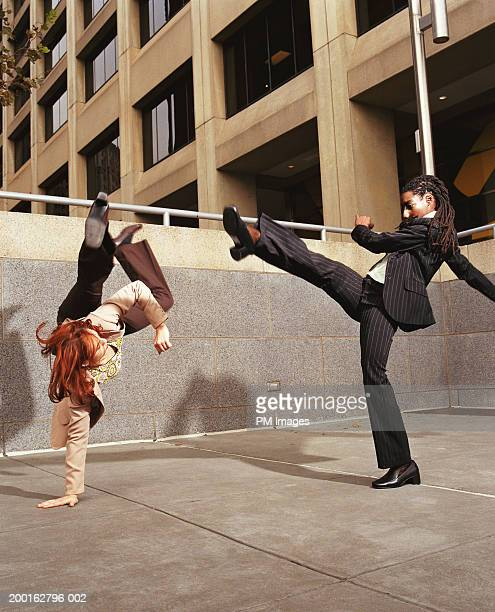 Two businesswomen fighting (Capoeira) in office plaza