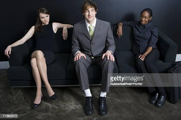 two businesswomen flirting with a businessman - フォーマルウェア ストックフォトと画像