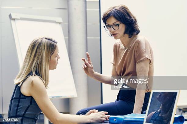 Two businesswomen having discussion in office meeting