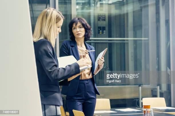 two businesswomen having discussion in open plan office - weibliche angestellte stock-fotos und bilder