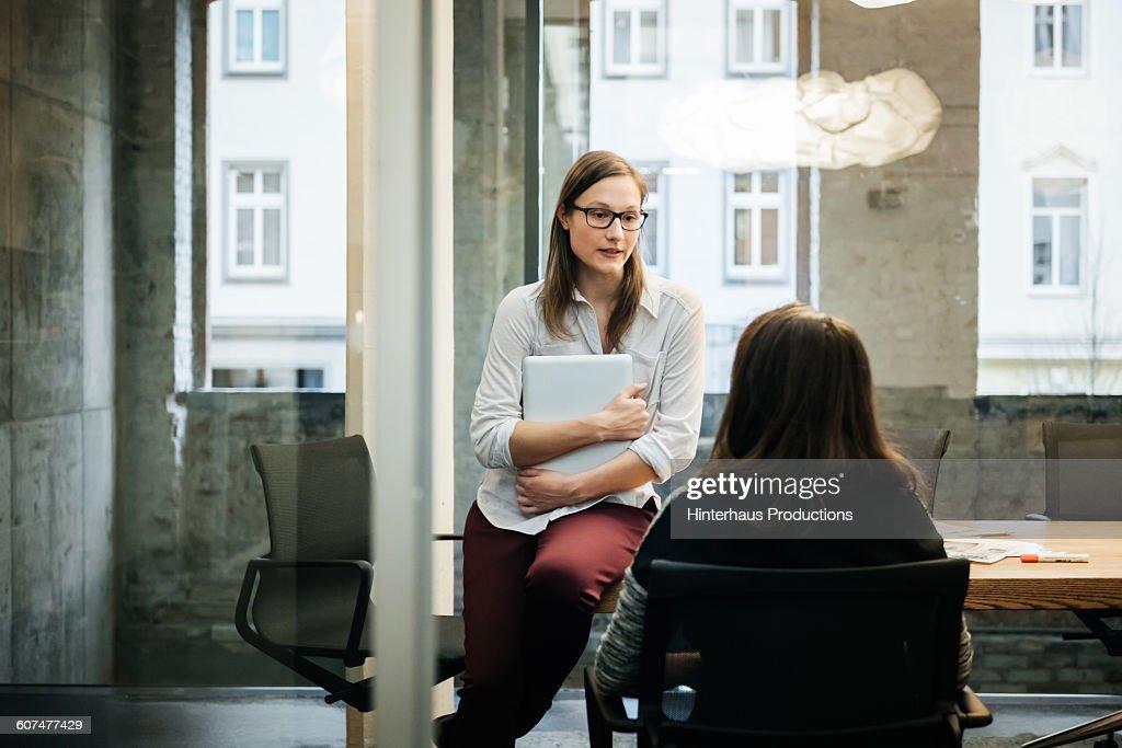 Two businesswomen in a modern office talking : Stock Photo