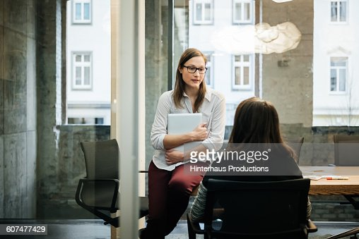 Two businesswomen in a modern office talking