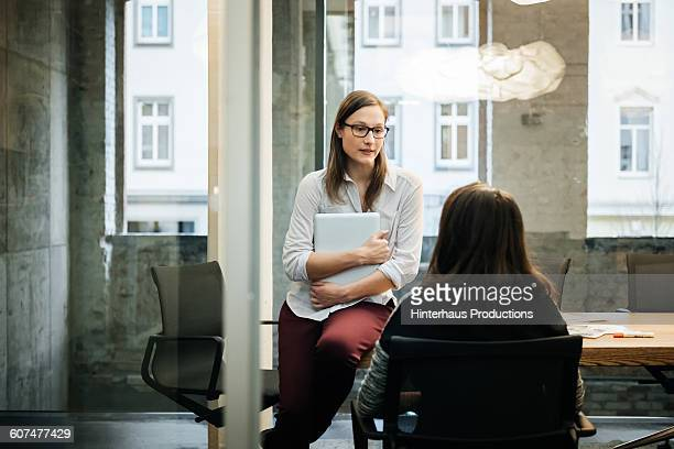 Two businesswomen in a modern office talking