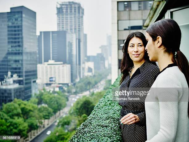Two businesswomen in discussion on office terrace