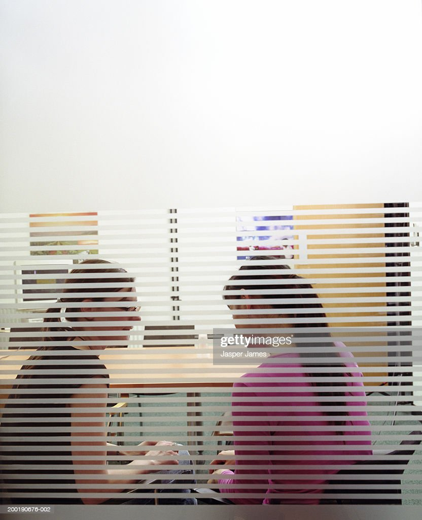 Two businesswomen in meeting room, view through glass : Stock Photo