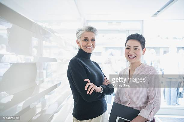 Two businesswomen in modern office, smiling