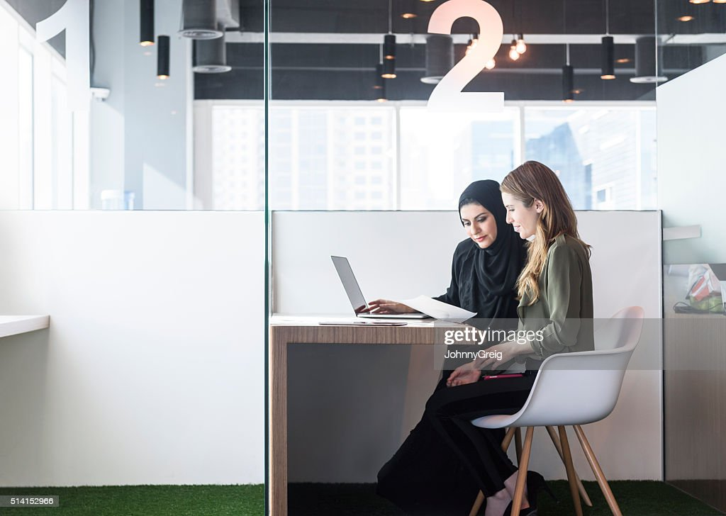 Two businesswomen in office cubicle, Dubai, UAE : Stock Photo