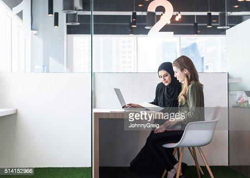 Two businesswomen in office cubicle, Dubai, UAE