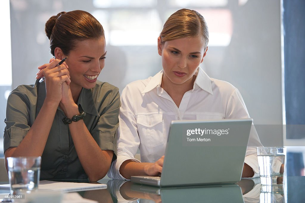 Two businesswomen in office with using laptop  : Stock Photo
