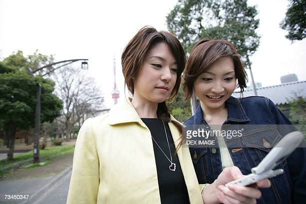 Two businesswomen looking at a mobile phone and smiling