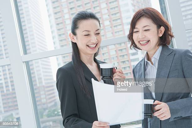 Two businesswomen looking at documents, smiling