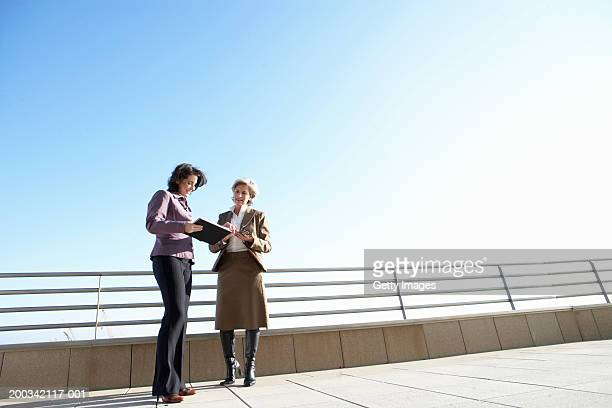 two businesswomen looking at folder outdoors, low angle view - older women in short skirts stock pictures, royalty-free photos & images