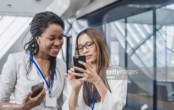 Dos empresarias mirando teléfono inteligente