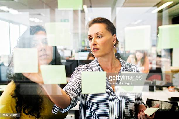 Two businesswomen looking over notes.