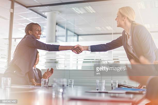 Two businesswomen shaking hands across a table