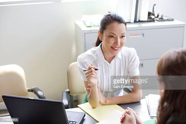 two businesswomen sitting at a table talking - overexposed stock photos and pictures