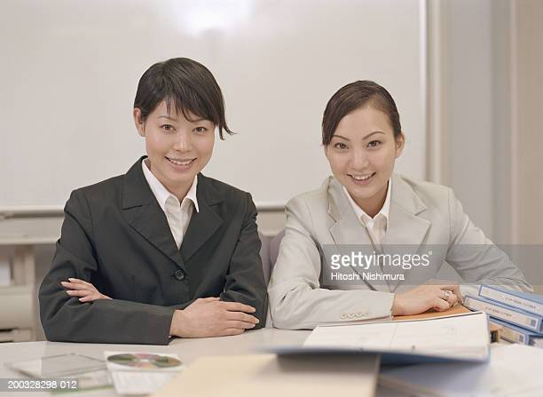 Two businesswomen sitting at conference table, smiling