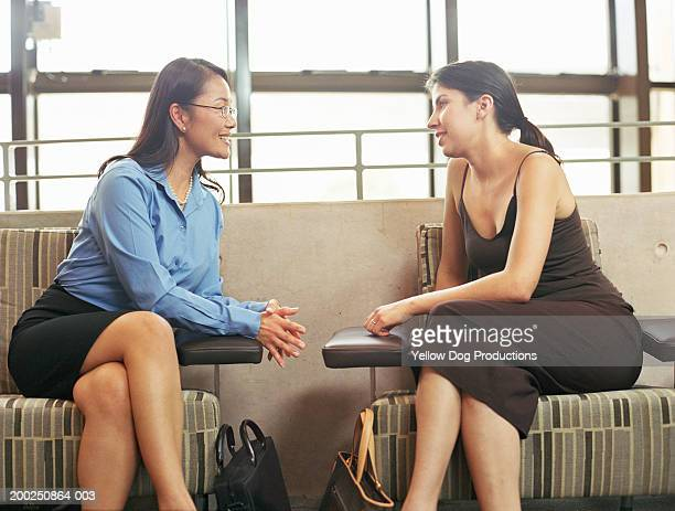 Two businesswomen sitting in lobby, talking, side view