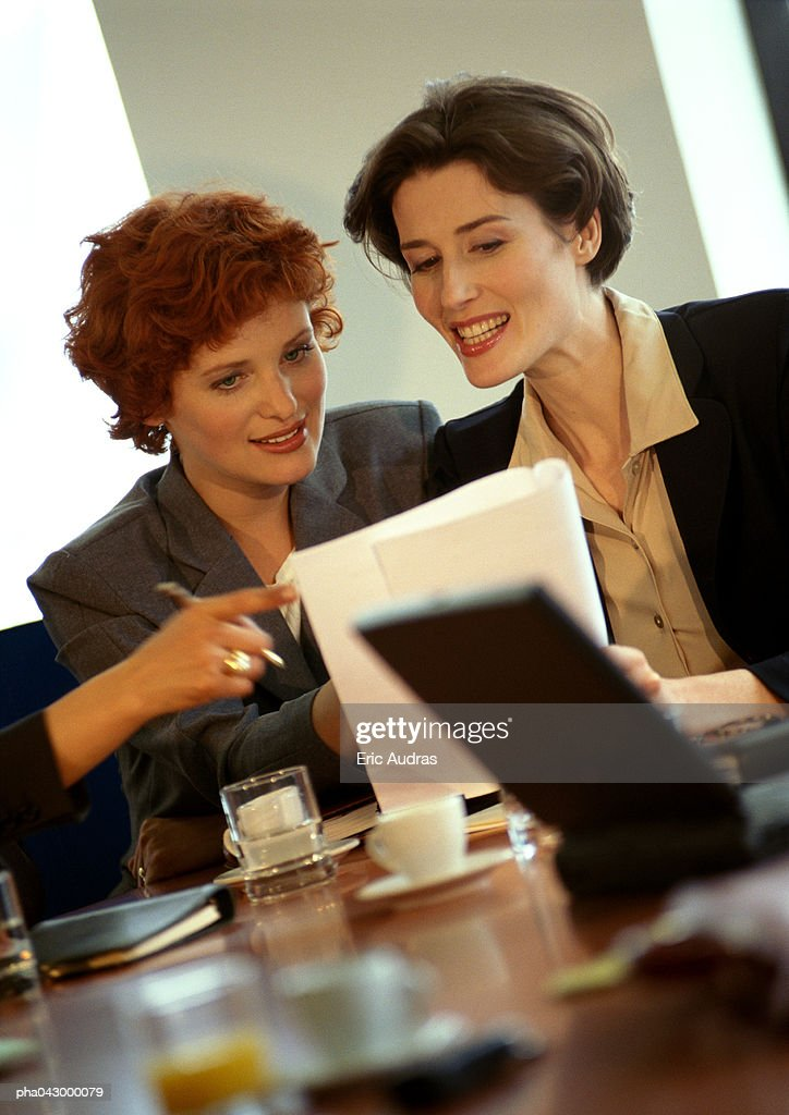 Two businesswomen sitting, looking at document : Stockfoto