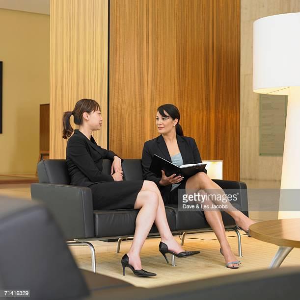 Two businesswomen sitting of sofa in lobby