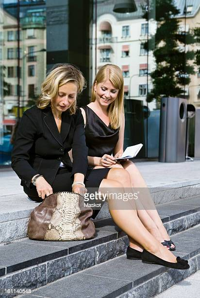 Two businesswomen sitting outside making plans