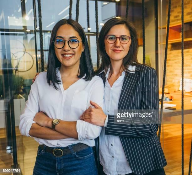 Zwei Geschäftsfrauen zusammenstehen im Bürogebäude