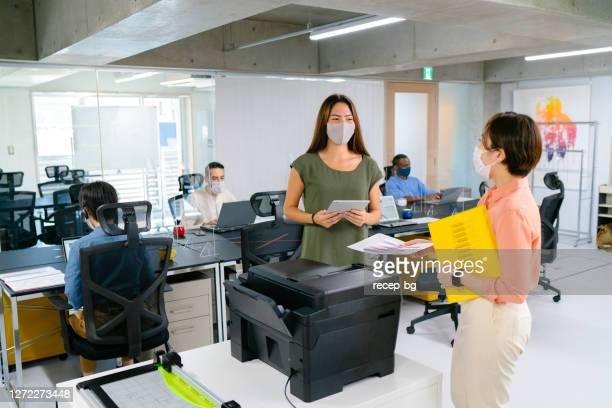 2人のビジネスウーマンがビジネスについて話し合い、他の同僚は保護フェイスマスクを着用しながら机で働き、くしゃみガードで机を分けることで社会的な離散を練習しています - 紙製備品 ストックフォトと画像