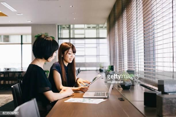 Twee vrouwelijke ondernemers praten in een modern kantoor
