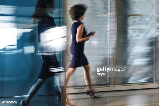 Two Businesswomen Walking Along The Corridor