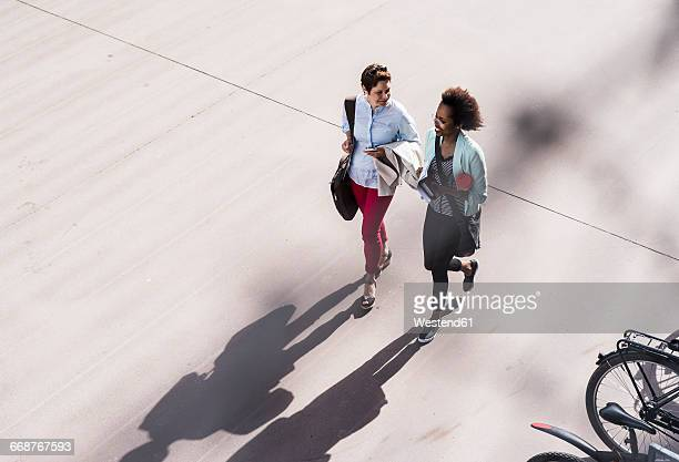 Two businesswomen walking and talking, seen from above