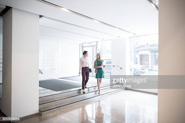 Two businesswomen walking down steps in modern office