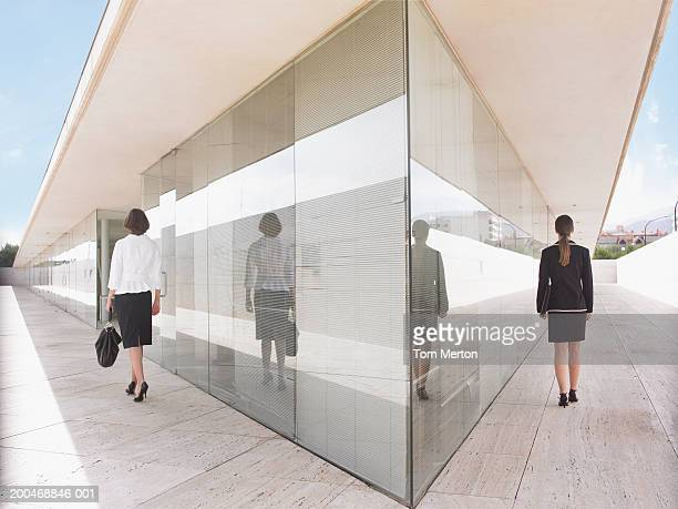 Two businesswomen walking either side of building, rear view