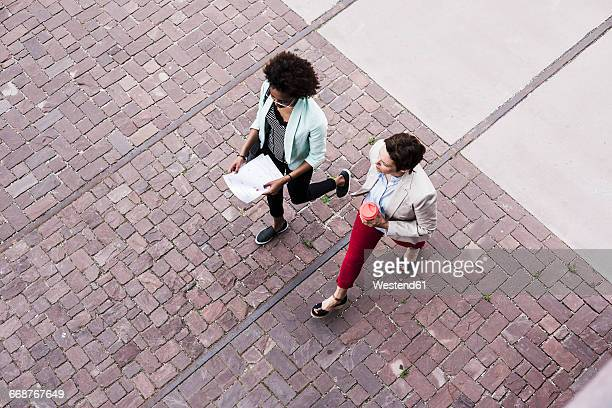 two businesswomen walking side by side, seen from above - panoramica verticale foto e immagini stock