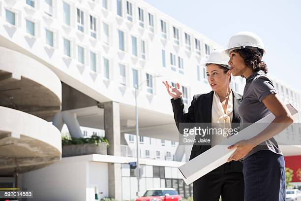 Two businesswomen, wearing hard hats, carrying plans