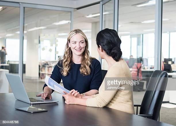Two businesswomen with documents and laptop in modern office