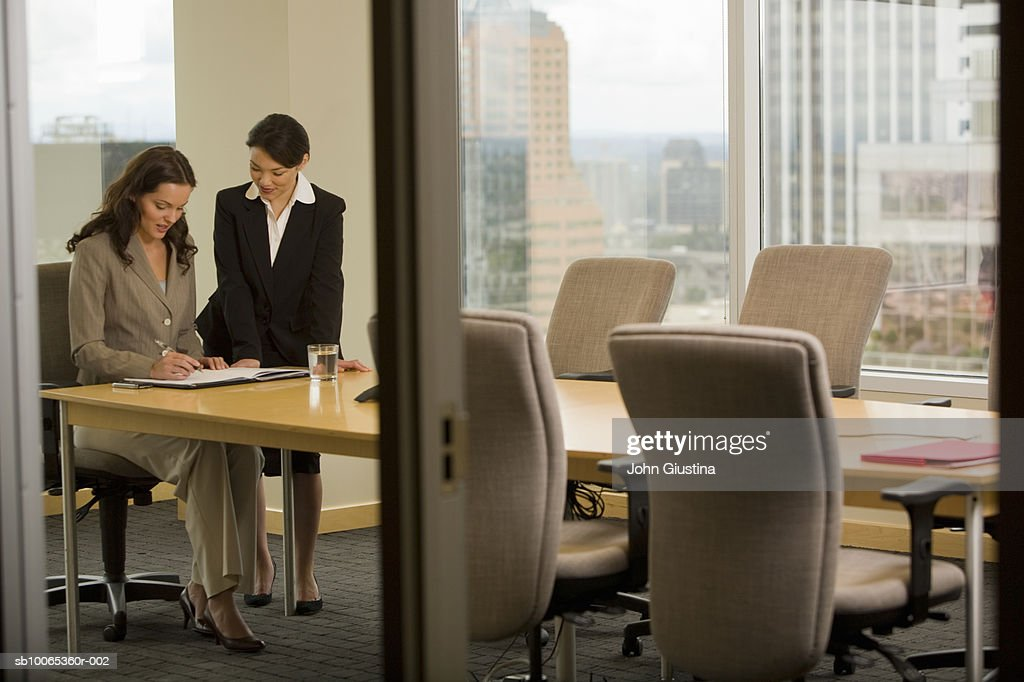 Two businesswomen working in conference room, smiling : Foto stock
